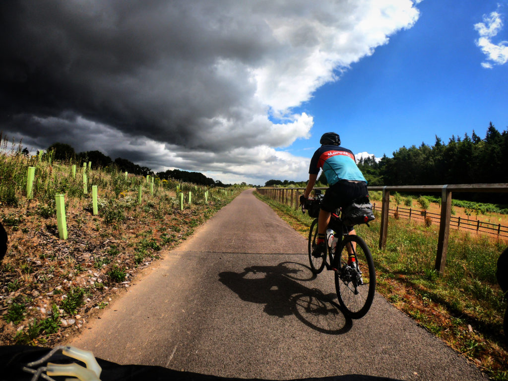 Cyclists riding into rain clouds